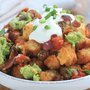 Tater Tot Nachos with Salsa Con Queso, Guacamole, Bacon, Salsa, Sour Cream and Green Onions