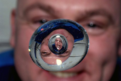 Astronaut Andre Kuipers watching a bubble float inside a drop of water