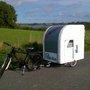 Lightweight caravan sleeps two adults, is towed by bicycle