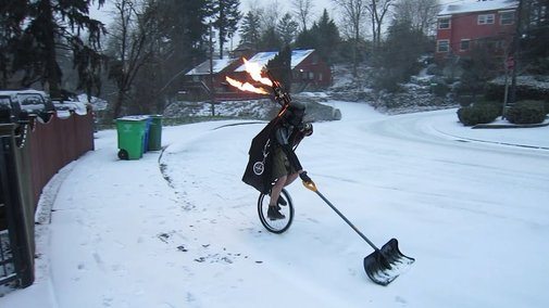 Man Shoveling Snow on a Unicycle Dressed as Darth Vader While Playing Flaming Bagpipes