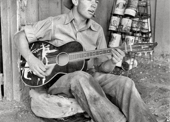 """""""Farm boy playing guitar in front of the filling station and garage."""" by Russell Lee"""