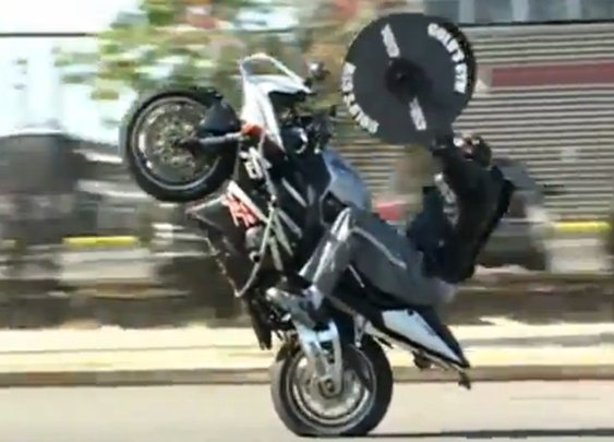 A man wheelies and bench presses..simultaneously