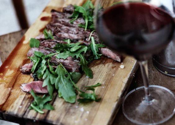 Sliced steak with red wine and wild rocket.