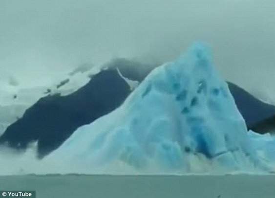 Tourist captures the incredible moment the bottom of an iceberg emerges from the ocean as it flips over (video)