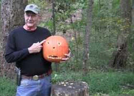 man uses pistol to carve pumpkin