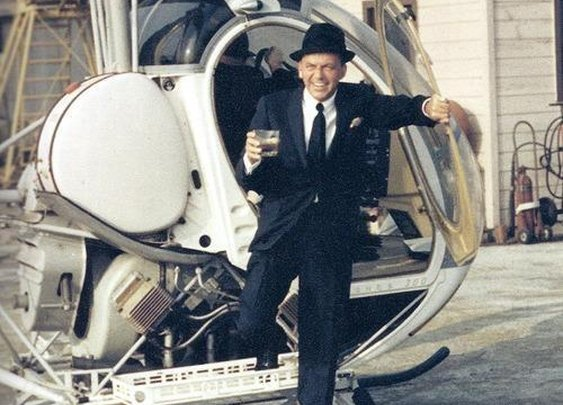 Frank Sinatra stepping off a helicopter with drink in hand
