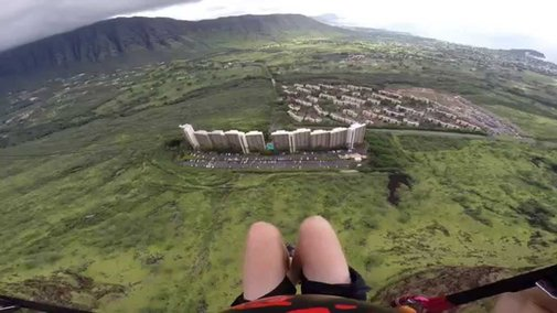 First-person Video of Paraglider Slicing Through a Gap in a Building