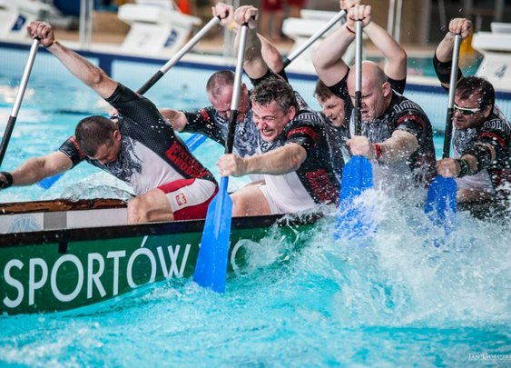 Two Teams at Opposite Ends of a Long Boat Play a Furious Game of Rowing Tug of War in an Indoor Pool