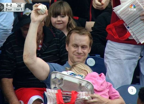Fan grabs foul ball while holding child and hot dogs