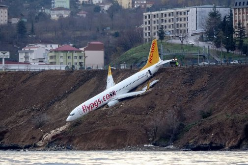 Plane skids off runway at Turkish airport, dangles off cliff near the sea.