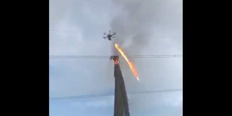 Drone with flamethrower clears debris from electrical wires