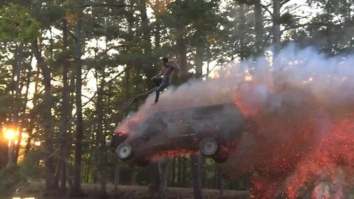 Stunt Video of a Man Driving an SUV Over a Hill of Fire and Jumping Out Just Before the Vehicle Lands in a Pond